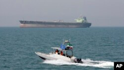 FILE - An Iranian Revolutionary Guard speedboat moves in the Persian Gulf while an oil tanker is seen in background, July 2, 2012. The United Arab Emirates said Wednesday that nine people held by Iran since January after being detained in the Persian Gulf have been freed.