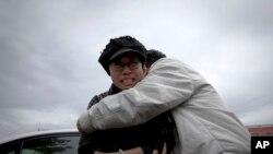 Seorang kerabat berupaya menenangkan Liu Xia (kiri), istri pemenang Nobel Perdamaian asal China yang dipenjara, Liu Xiaobo, saat menangis di luar penjara Huairou, luar kota Beijing, China (9/6). Kakak Liu Hua, Liu Hui, divonis penjara 11 tahun terkait tuduhan melakukan kecurangan dalam masalah perumahan. (9/6).