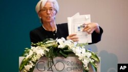 International Monetary Fund (IMF) Managing Director Christine Lagarde holds a document report while speaking during a session of the G20 High-Level Seminar on Structural Reform, proceeding the G20 Finance Ministers and Central Bank Governors Meeting at th