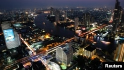 FILE - Cars and trains move on Taksin bridge over Chao Phraya river in central Bangkok, at sunset, March 14, 2013.