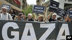 US activists chant slogans as they hold placards after a news conference about an international flotilla to blockaded Gaza, in Athens, June 27, 2011