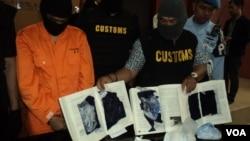 Terduga pengedar narkoba (kiri) bersama petugas bea cukai yang memperlihatkan buku yang dilubangi untuk menyelundupkan narkoba jenis shabu-shabu ke Solo (30/12). (VOA/Yudha Satriawan)