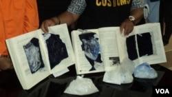 Petugas bea cukai yang memperlihatkan buku yang dilubangi untuk menyimpan narkoba jenis shabu-shabu yang diselundupkan ke Solo (Foto: dok). Enam terpidana penyelundup narkoba, termasuk lima warga asing, dijadwalkan akan dihukum mati, Minggu (18/1).
