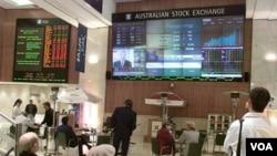Sekelompok pria menyaksikan naik turunnya bursa di pasar saham Australia