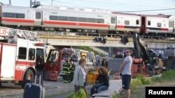 Para penumpang menunggu kendaraan angkutan lain, setela kereta komuter yang mereka naiki kecelakaan di Bridgeport, Connecticut (17/5). Dilaporkan 60 orang cedera dalam musibah tersebut.