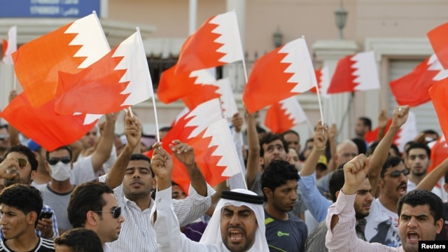 Anti-government protesters shout slogans while holding Bahraini flags during a protest outside Bahrain's leading opposition party Al Wefaq's headquarters in Manama, May 9, 2012.