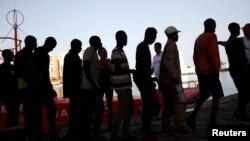 Les migrants interceptés à bord d'un canot au large de la côte méditerranéenne, quittent un bateau de sauvetage à leur arrivée au port de Malaga, dans le sud de l'Espagne, le 7 juillet 2018.