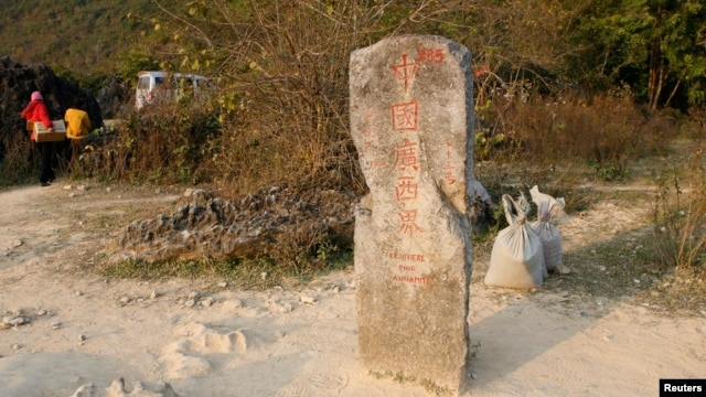 FILE - Chinese business women walk near old border marker 53 between China's Guangxi and Vietnam's Cao Bang province.