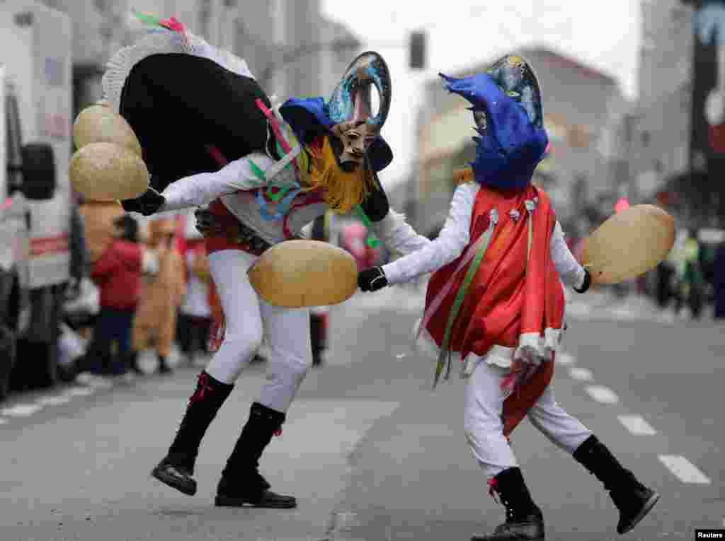 Revelers strike each other with pig bladders on a street during carnival celebrations in the northwestern village of Xinzo de Limia, Spain.