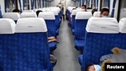 湖北武昌火車站裡戴著口罩的旅客在火車車廂裡休息。 (2020年4月8日)