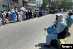 Afghans line up outside a bank to take out their money after Taliban takeover in Kabul, Sept. 1, 2021.