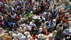 一名在印度东北部的曼尼普尔邦被反政府分子袭杀的军人家属和其他人士聚集在他的遗体身旁。(2015年6月7日)