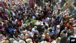 一名在印度東北部的曼尼普爾邦被反政府分子襲殺的軍人家屬和其他人士聚集在他的遺體身旁。(2015年6月7日)