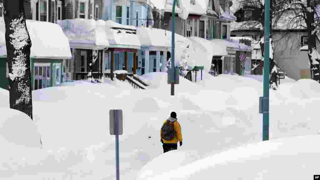 Brian Cintron marche dans son quartier de Buffalo sud couvert de neige, jeudi 20 novembre 2014, à Buffalo, NY. Une tempête de neige s'est abattue sur Buffalo pour la troisième journée consécutive causant plus de misère à une ville déjà enterrée par une tombée de neige meurtrière qui pourrait laisser quelques zones avec près de 2,5 mètres de neige.
