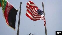 Trực thăng Chinook bay giữa quốc kỳ Mỹ và Afghanistan trong buổi lễ chuyển giao quyền kiểm soát an ninh ở thị trấn Bazarak trong tỉnh Panjshir, phía bắc thủ đô Kabul, ngày 24/7/2011