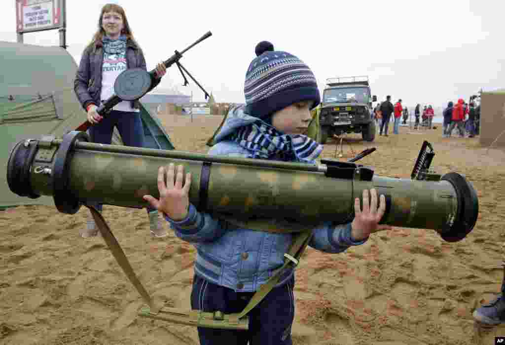A boy holds a Russian anti-tank missile at a weapon exhibition during a military sports festival marking the Day of Russia, in St.Petersburg.