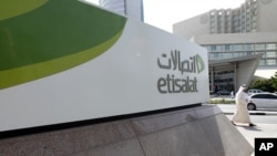 A man walks past a sign at the headquarters of telecommunications company Etisalat in Dubai (2011 File)