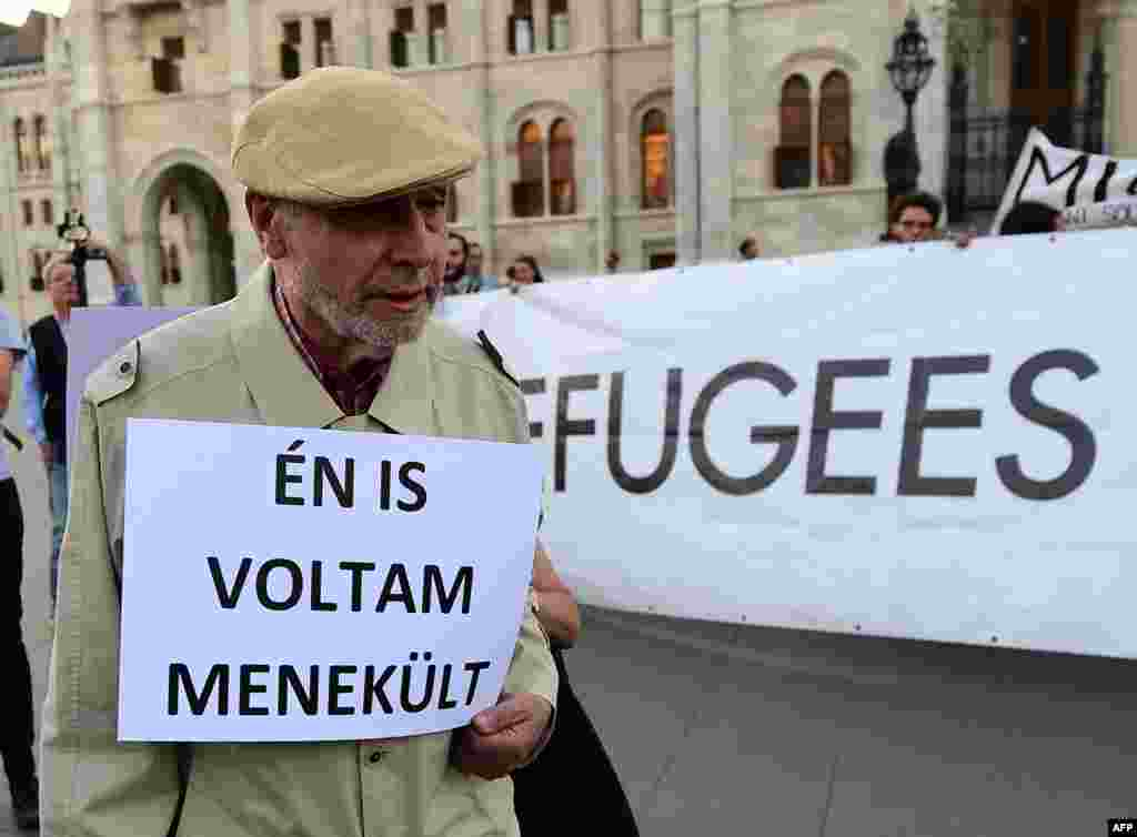 "An elderly man walks with his placard with text, ""I was refugee also,"" as activists hold up a banner with 'Refugees welcome' during protests against the migration policy of the Orban government in front of the parliament building in Budapest.  A referendum on the EU's migrant resettlement plans will be held on Sunday in Hungary."