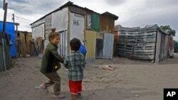 ເດັກນ້ອຍຫລີ້ນນໍາກັນ ຢູ່ນອກຕູບຫລັງນຶ່ງ ໃນຄຸ້ມຄົນທຸກ ນອກເມືອງ Cape Town ປະເທດອາຟຣິກາໃຕ້.