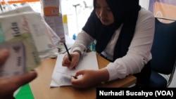 Seorang anggota staf mencatat data KTP pembeli masker di sebuah apotek di Yogyakarta, Sabtu, 14 Maret 2020. (Foto: Nurhadi Sucahyo/VOA)