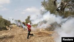 Seorang demonstran Palestina melemparkan kembali gas air mata yang ditembakkan oleh tentara Israel dalam bentrokan akibat ketegangan di Masjid al-Aqsa, Yerusalem, di desa Budrus dekat Ramallah, 2 Oktober 2015.