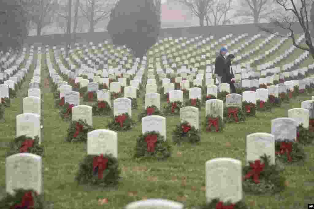 """Pessoas caminham entre as lápides adornadas com as coroas no cemitério nacional de Arlington durante o Dia das Coroas na América ou em inglês """"Wreaths Across America Day"""" em Arlington, no estado da Virgínia, 14 de Dez de 2019."""