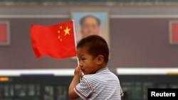 在天安门毛主席像前,小男孩举着中国国旗。在这个小男孩的有生之年,天安门毛像会拆除吗