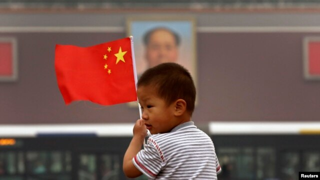 A child holds a Chinese national flag in front of a portrait of China's late Chairman Mao Zedong at Tiananmen Square in Beijing, June 4, 2013.