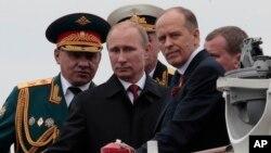 Tổng thống Nga Vladimir Putin cùng với Bộ trưởng Quốc phòng Sergei Shoigu (trái) và Giám đốc Cơ quan An ninh Alexander Bortnikov (phải) trên 1 chiếc thuyền ở Sevastopol, Crimea, 9/5/2014.