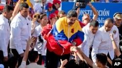 រូបភាពឯកសារ៖ប្រធានាធិបតីវ៉េណេស៊ុយអេឡា Nicolas Maduro (កណ្តាល) ព័ទ្ធដោយក្រុមកងអង្គរក្ស ចាប់ដៃជាមួយអ្នកគាំទ្រនៅក្នុងការដើរប្រឆាំងអាមេរិកនៅក្នុងទីក្រុង Carcacas ប្រទេសវ៉េណេស៊ុយអេឡា កាលពីថ្ងៃច័ន្ទ ទី១៥ ខែធ្នូ ឆ្នាំ២០១៤។