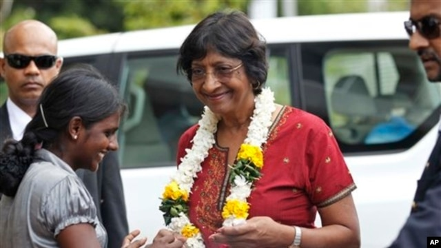 Ethnic Tamil girl presents floral garland to welcome U.N. High Commissioner for Human Rights, Navi Pillay, Kilinochchi, Sri Lanka, Aug. 27, 2013.