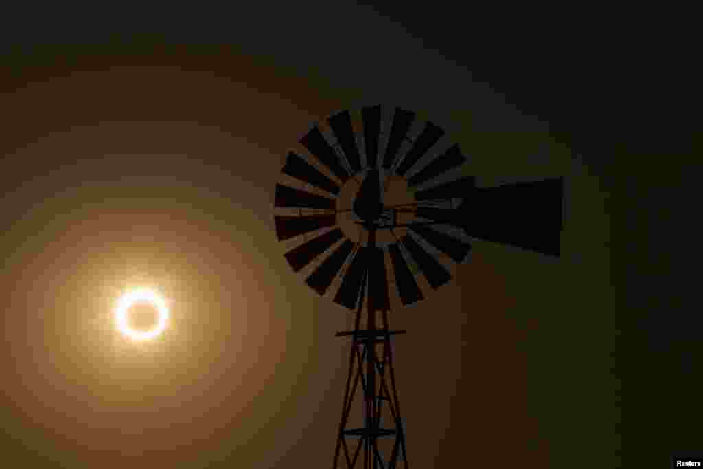 La Luna pasa entre el sol y la tierra detrás de un molino de viento en Albuquerque, Nuevo México.