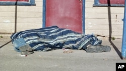 In this Aug. 9, 2013, photo homeless people cover themselves with a blanket on a street in Whiteclay, Neb. Many tribal members live on the tiny town's barren streets to avoid arrest on the nearby reservation for being intoxicated.