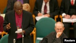 The Archbishop of York, John Sentamu (L), speaks next to the Archbishop of Canterbury Justin Welby at the General Synod in Church House in central London, England, Nov. 20, 2013