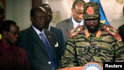 Presiden Sudan Selatan Salva Kiir (kanan) hari Senin (16/12) di Juba, mengumumkan gagalnya upaya kudeta hari Minggu malam oleh pasukan pendukung mantan Wapres Riek Machar.