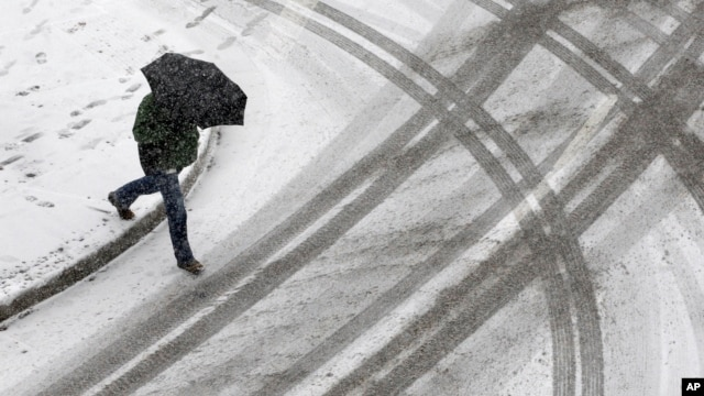 A man crosses the street as a light snow falls in Baltimore, Maryland, Jan. 21, 2014.