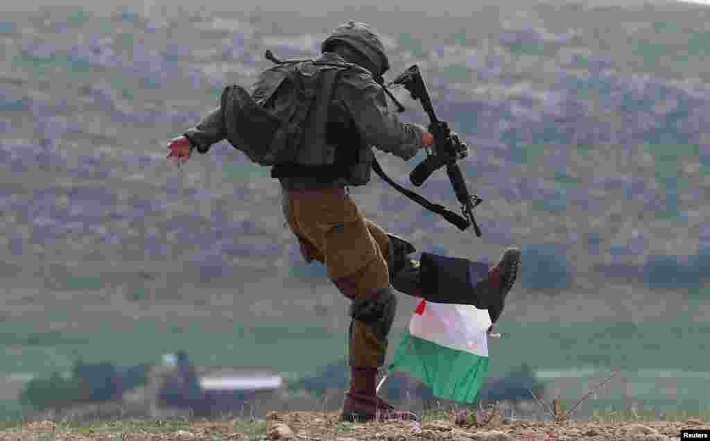 An Israeli soldier kicks a Palestinian flag during a protest against the U.S. president Donald Trump's Middle East peace plan, in Jordan Valley in the Israeli-occupied West Bank.