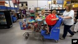 FILE - A family shops at the Wal-Mart Supercenter in Springdale, Arkansas, June 4, 2015. Consumer spending that powers most U.S. econometric activity jumped a strong one percent in April, the biggest gain in about six years.