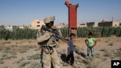 Tentara AS berdiri di dekat beberapa anak Suriah di jalan yang menghubungkan ke Raqqa, Suriah, 26 Juli 2017