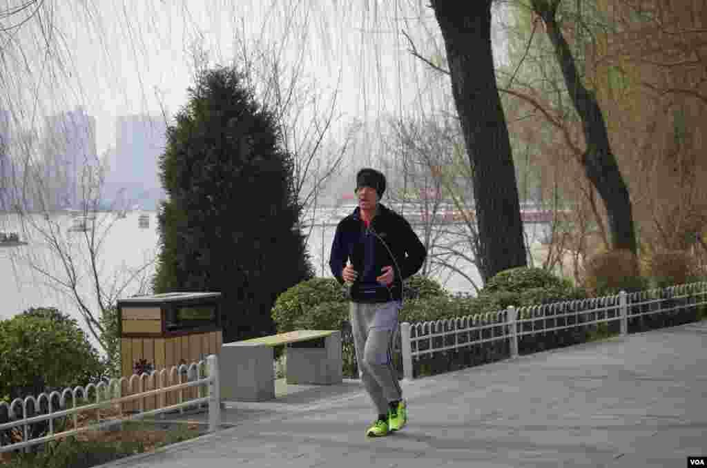 尽管雾霾严重,仍有市民不畏恶劣天气在湖边坚持锻炼 (曾谙 摄于2016年3月21日)