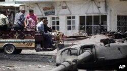 'Yan Syria su na kallon wani tankin sojojin gwamnati da 'yan tawaye suka ragargaza a garin Ariha dake wajen Idlib a arewacin Syria a ranar lahadi 10 Yuni 2012