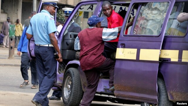 A September 2006 file photo shows a Kenyan policeman boarding a minibus  after the vehicle was stopped for a traffic offence in the capital Nairobi.