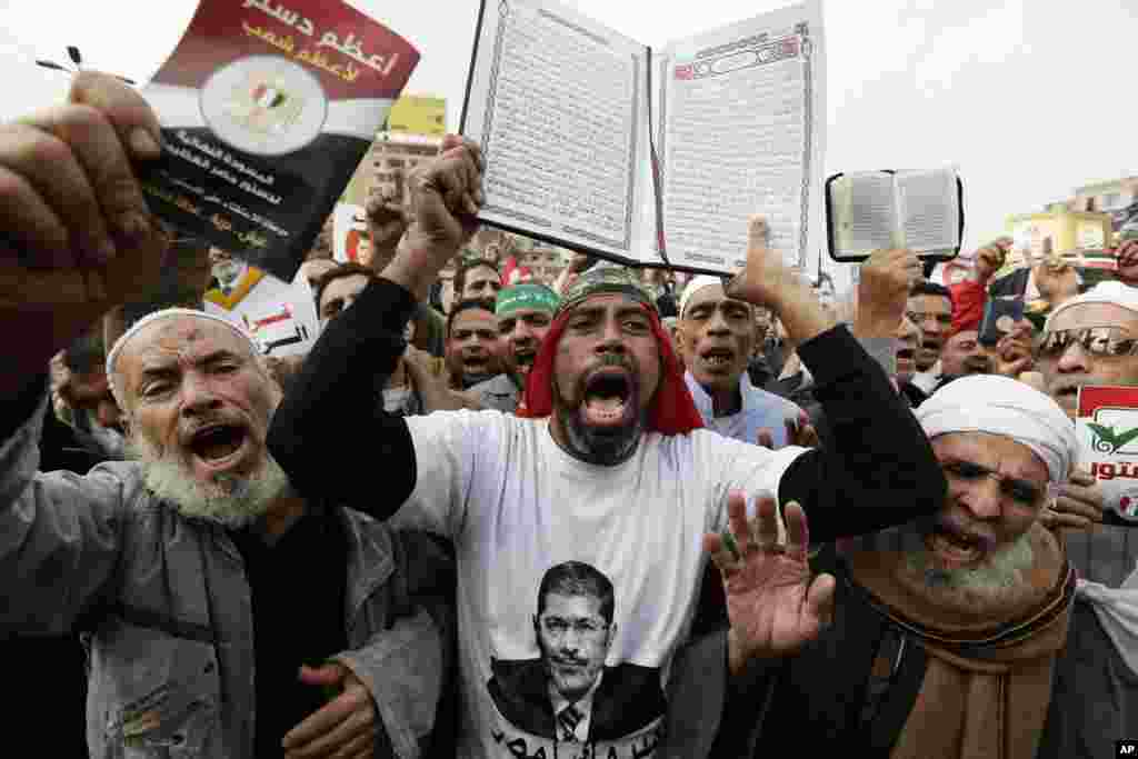 Supporters of Egyptian President Mohammed Morsi chant slogans as one holds up the Quran, Islam's holy book, during a demonstration after the Friday prayer, in Cairo, Egypt, Dec. 14, 2012.