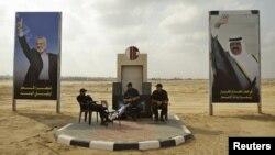 Các thành viên của lực lượng an ninh Hamas ngồi giữa các áp phích hình thủ lãnh nhóm Hamas Ismail Haniyeh (trái) và Quốc vương Qatar Emir Sheik Hamad bin Khalifa al-Thani tại Khan Younis, miền nam Dải Gaza