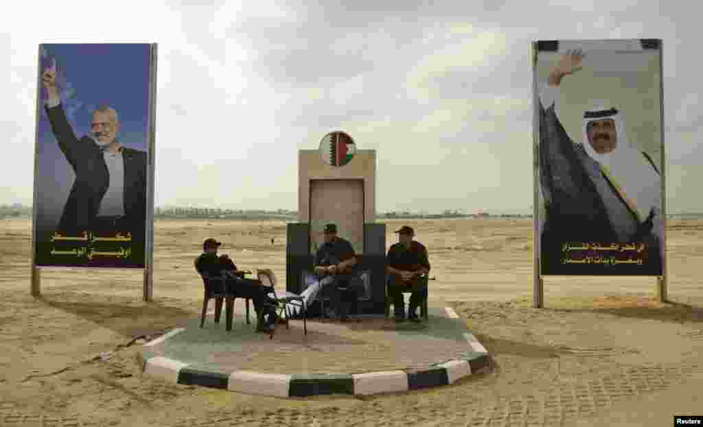 Members of Hamas security forces sit between posters depicting senior Hamas leader Ismail Haniyeh (L) and Qatar's Emir Sheik Hamad bin Khalifa al-Thani (R) in Khan Younis in the southern Gaza Strip October 22, 2012.