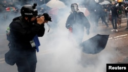 """一名頭戴標有""""媒體""""字樣頭盔,前胸掛記者證的攝影記者在催淚彈的煙霧中拍攝香港的反送中抗議。(2019年10月6日)"""