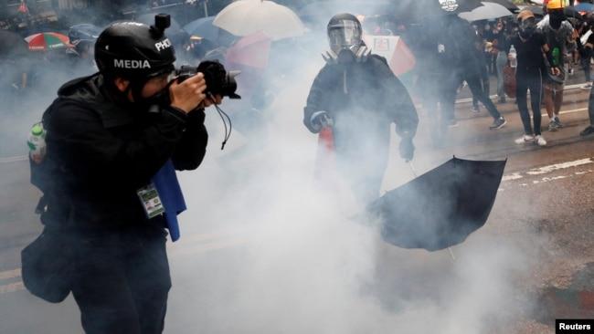 """一名头戴标有""""媒体""""字样的摄影记者在催泪弹的烟雾中拍摄香港的反送中抗议。(2019年10月6日)"""