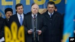 El senador John McCain, centro, habla junto a su colega demócrata Chris Murphy y el líder opositor ucraniano Oleh Tyahnybok, en la Plaza de la Independencia de Kiev.