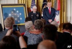 President Donald Trump stands on stage before bestowing the nation's highest military honor, the Medal of Honor, to retired Army medic Jim McCloughan, left, during a ceremony in the East Room of the White House in Washington, July 31, 2017.