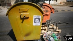 """A Gadhafi """"Wanted"""" sign on the side of a trash can in Tripoli."""